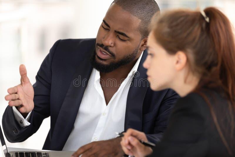 教有计算机的非裔美国人的商人辅导者白种人实习生 免版税库存图片
