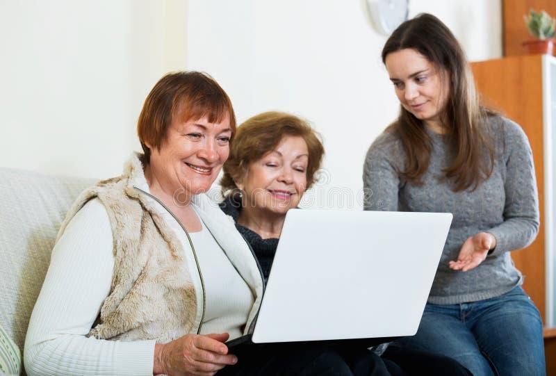 教正面资深妇女的微笑的逗人喜爱的女孩使用膝上型计算机 免版税库存照片