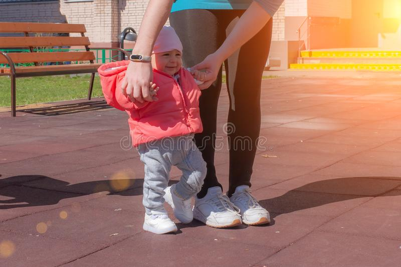 教的母亲抱着她的桃红色的婴孩用人工和做第一步 妈妈和婴儿女孩步行在操场在好日子 免版税库存图片