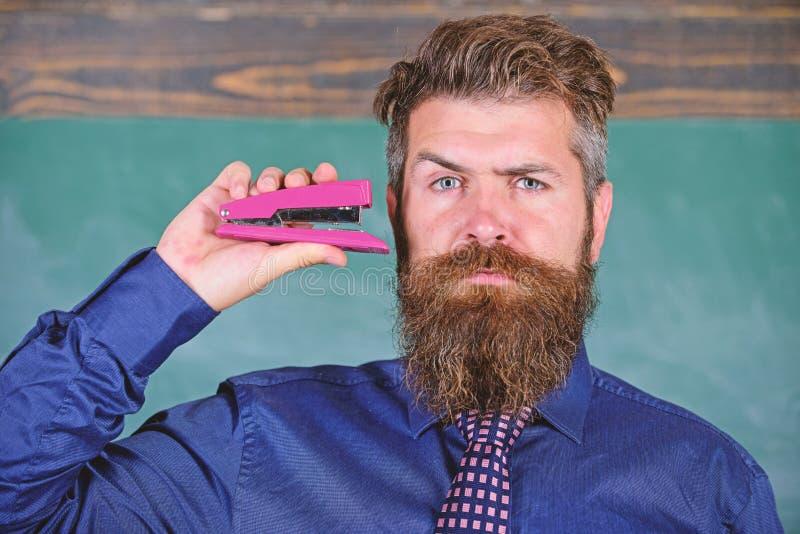 教的熟记技术 与脖子领带的行家老师礼服拿着订书机 回到学校和学习 图库摄影