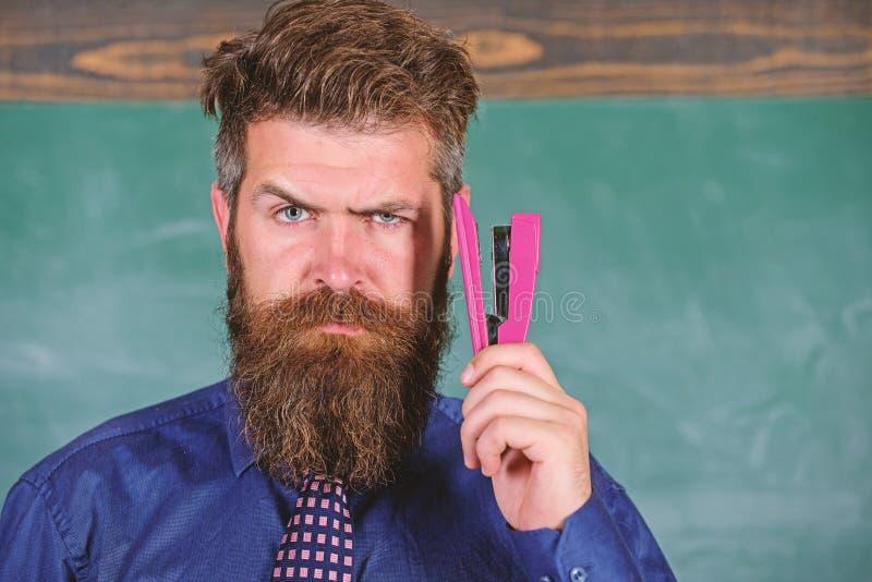 教的熟记技术 回到学校和学习 有桃红色订书机黑板的老师有胡子的人 免版税库存照片