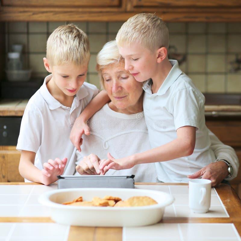 教祖母的孩子使用片剂个人计算机 免版税库存图片