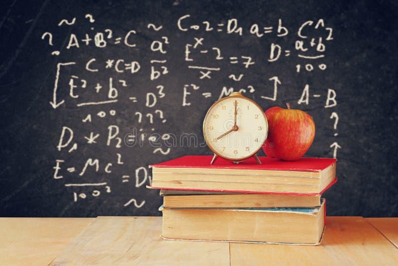 教科书的图象在木书桌上的,苹果和葡萄酒计时在与惯例的黑背景 登记概念教育查出的老 免版税图库摄影