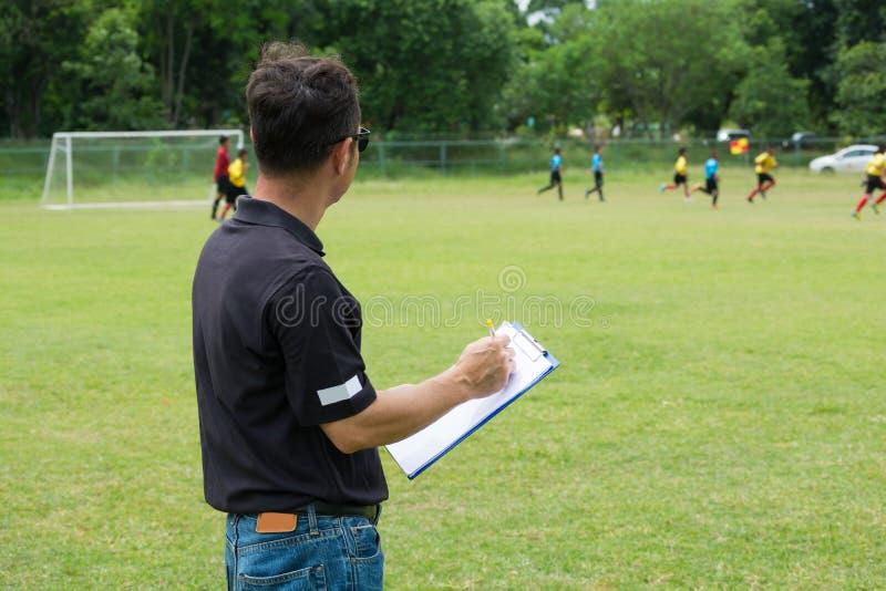 教练他的在橄榄球或足球场旁边的球队教练乘员组 免版税库存照片