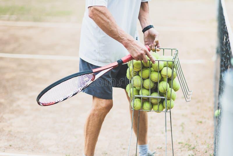 教练在训练以后收集网球在篮子的球 网球课 免版税库存图片