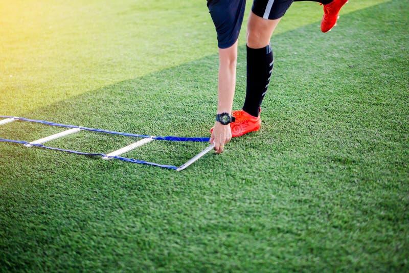 教练投入足球trainng的梯子钻子能跑和跳 E 库存照片