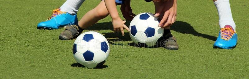 教练教孩子使用与球、腿和球 库存照片