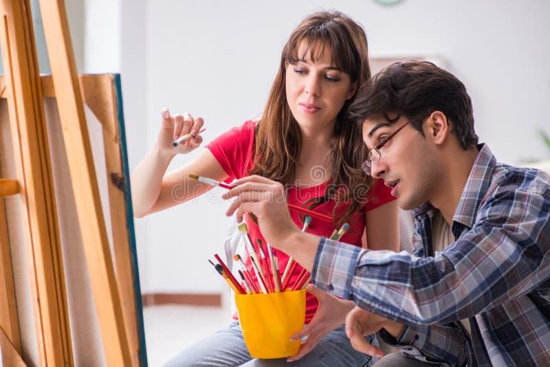 教练绘画类的艺术家学生在演播室 免版税库存照片