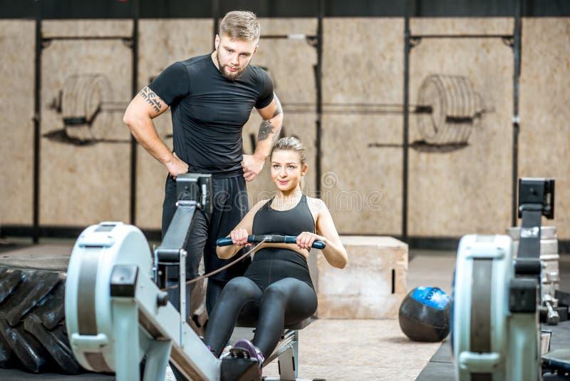 教练锻炼机器的训练妇女 免版税库存照片