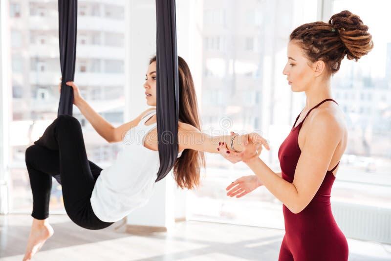 教美丽的女孩的严肃的少妇教练员做空中瑜伽 图库摄影
