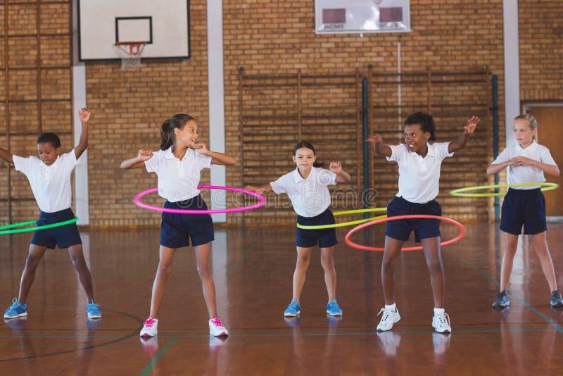 教育使用与hula箍的孩子在篮球场 免版税库存图片