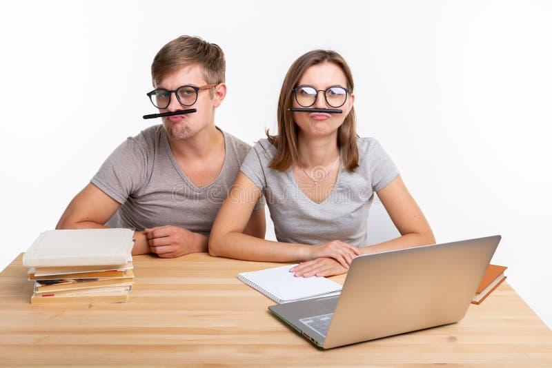 教育和人概念-玻璃的两三名年轻学生看,如他们乏味学会家庭作业和 库存照片