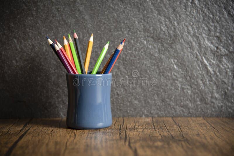 教育和回到与铅笔的学校概念五颜六色在黑暗的背景-木蜡笔的笔匣 库存照片