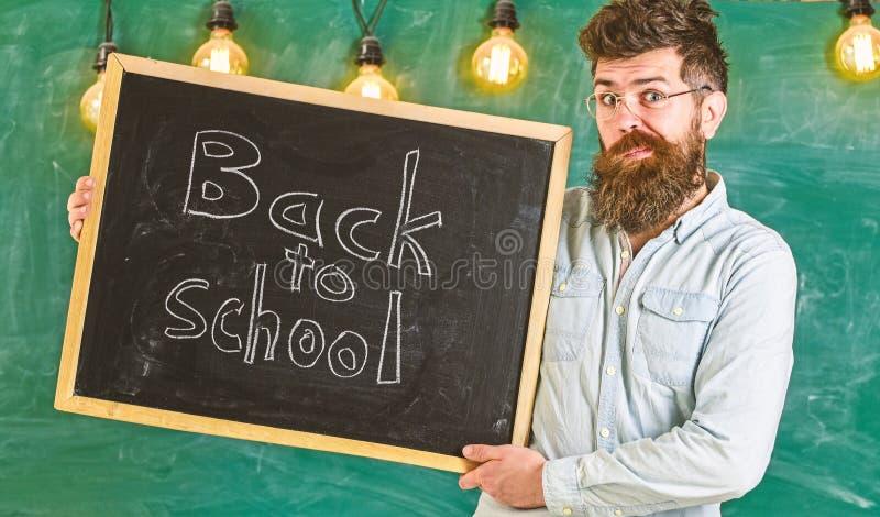 教育和学习概念 有胡子的有鬼脸的在面孔欢迎学生,黑板人和髭 库存照片