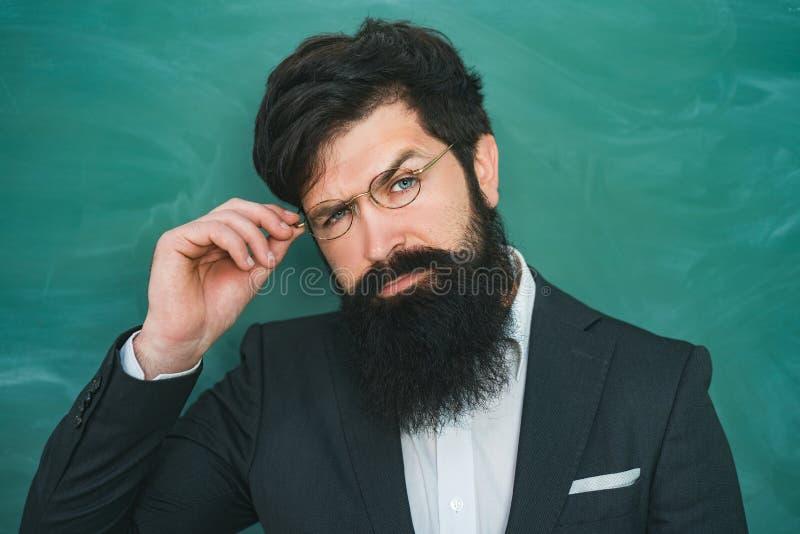 教育和学会人概念-在黑板附近的女老师 学校教训的有胡子的教授在书桌 免版税库存照片