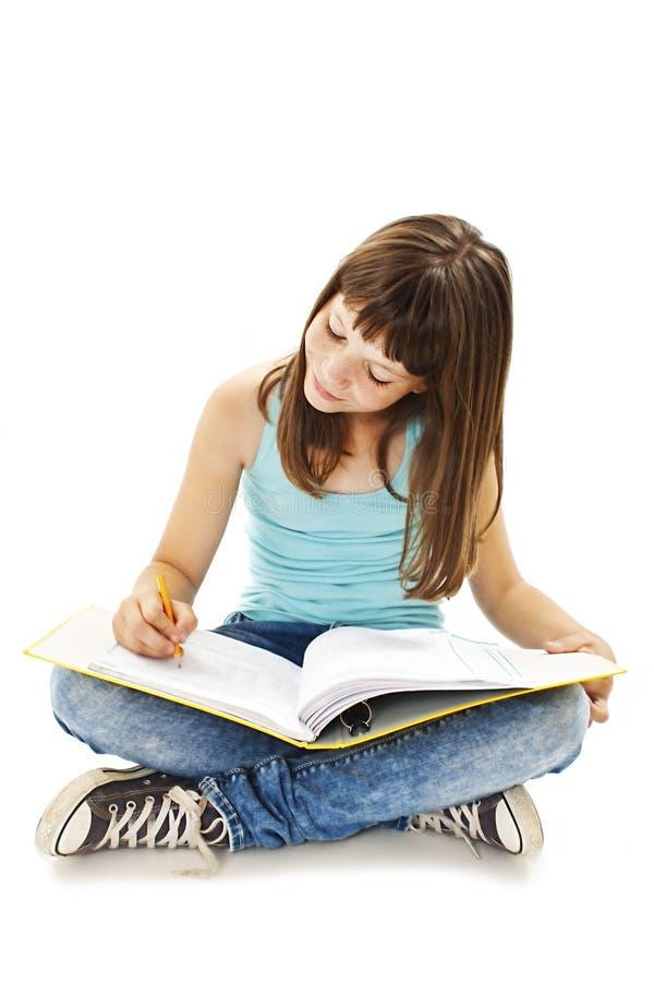 教育和学校概念-小学生女孩坐地板和阅读书 库存图片