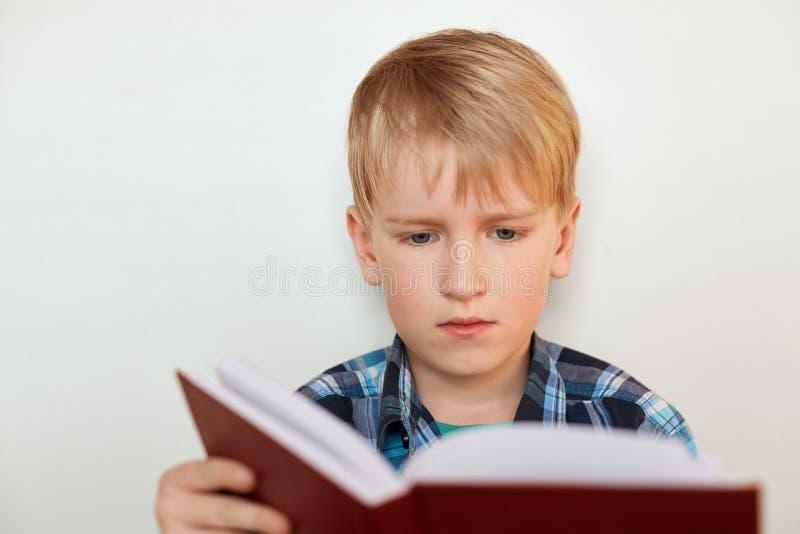 教育和学校概念 逗人喜爱的男小学生画象有在控制中衬衣举行穿戴的金发和attrractive蓝眼睛的 免版税图库摄影