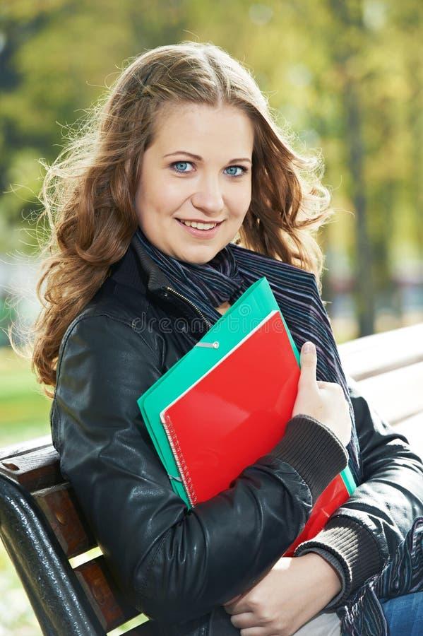 教育和研究 女性愉快的学员 有笔记本和作业簿的女孩在户外公园 库存照片