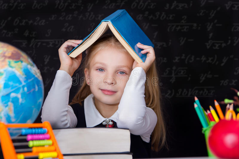 教育女孩在有书的一张书桌坐她的头 免版税库存照片