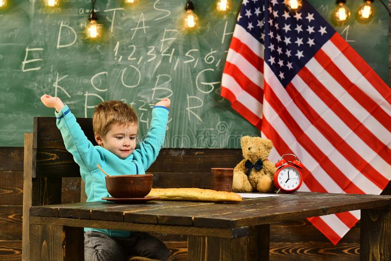 教育孩子在教训在7月第4 美国的愉快的独立日 回到学校或家教 小男孩吃 图库摄影