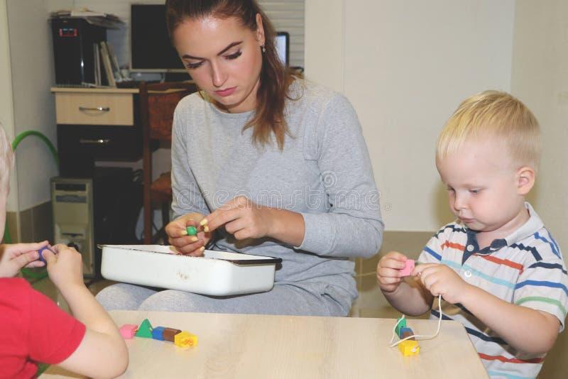 教育家处理孩子在幼儿园 孩子的创造性和发展 免版税图库摄影