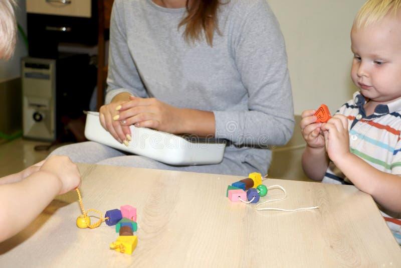 教育家处理孩子在幼儿园 孩子的创造性和发展 库存照片