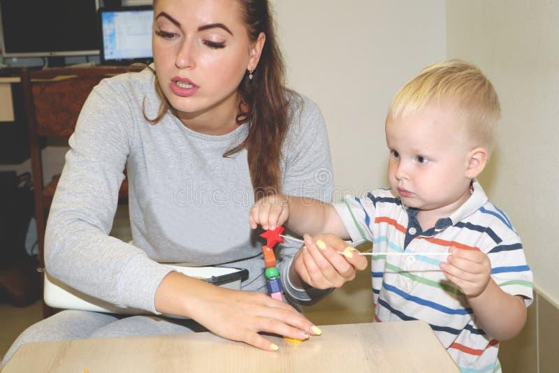 教育家处理孩子在幼儿园 孩子的创造性和发展 图库摄影