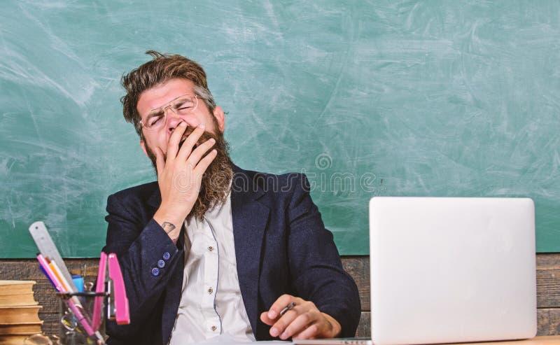 教育家更被注重在工作比普通人 高级疲劳 教育家有胡子的人打呵欠的面孔疲倦了在工作 库存照片