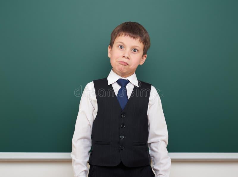 教育摆在学生的男孩并且认为在干净的黑板,做鬼脸和情感,穿戴在一套黑衣服,教育概念, s 库存图片