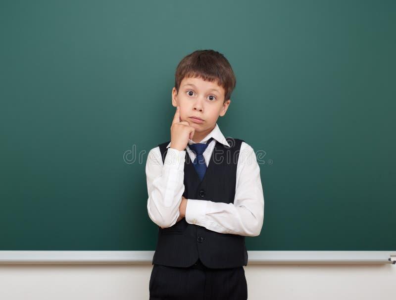 教育摆在学生的男孩并且认为在干净的黑板,做鬼脸和情感,穿戴在一套黑衣服,教育概念, s 免版税库存照片