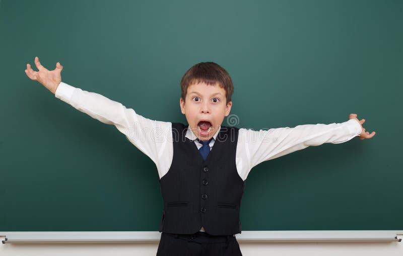 教育摆在干净的黑板和开放胳膊,做鬼脸和情感的学生男孩,穿戴在一套黑衣服,教育concep 库存图片