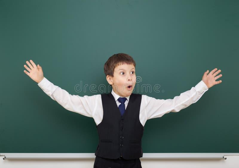 教育摆在干净的黑板和开放胳膊,做鬼脸和情感的学生男孩,穿戴在一套黑衣服,教育concep 免版税库存图片