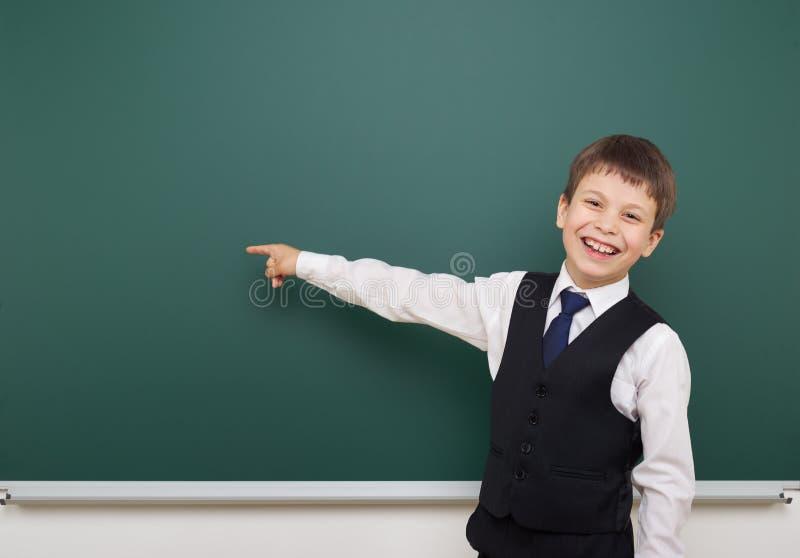 教育摆在干净的黑板的学生男孩,显示手指并且指向在,做鬼脸和情感,穿戴在一套黑衣服, educ 库存照片