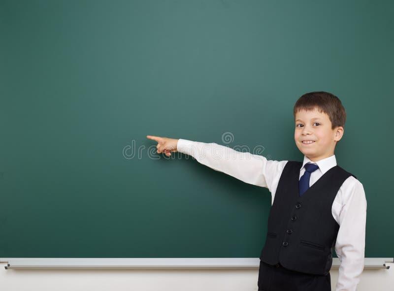 教育摆在干净的黑板的学生男孩,显示手指并且指向在,做鬼脸和情感,穿戴在一套黑衣服, educ 图库摄影