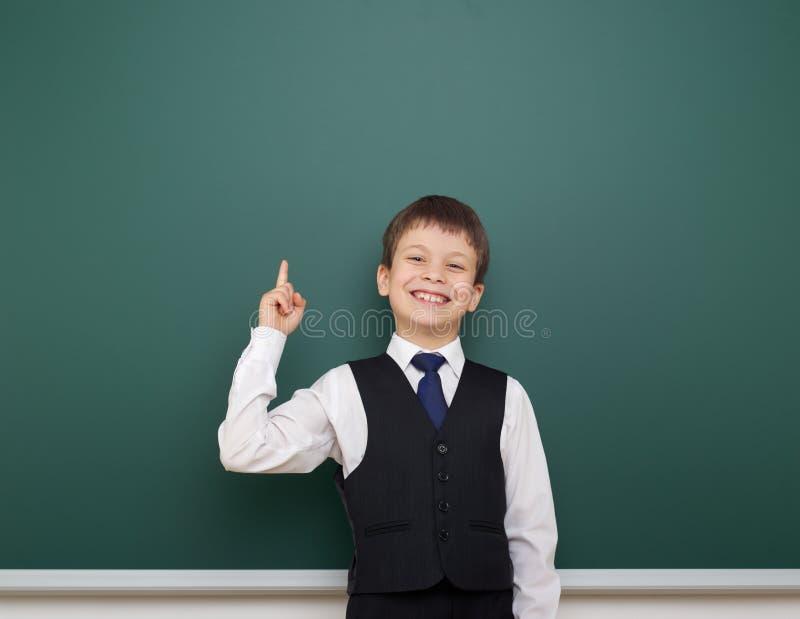 教育摆在干净的黑板的学生男孩,显示手指并且指向,做鬼脸和情感,穿戴在一套黑衣服, educ 免版税库存照片