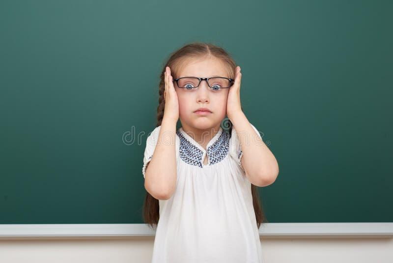教育摆在干净的黑板,做鬼脸和情感的学生女孩,穿戴在一套黑衣服,教育概念,演播室pho 库存图片