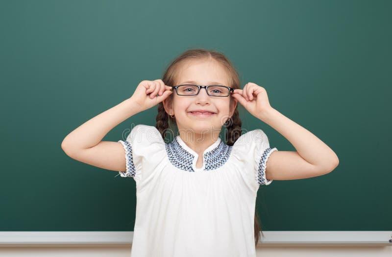 教育摆在干净的黑板,做鬼脸和情感的学生女孩,穿戴在一套黑衣服,教育概念,演播室pho 库存照片
