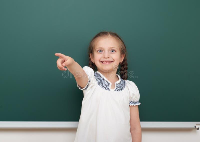 教育摆在干净的黑板,做鬼脸和情感的学生女孩,穿戴在一套黑衣服,教育概念,演播室pho 免版税图库摄影