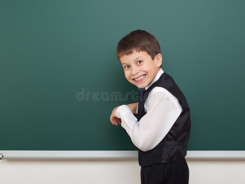 教育摆在干净的黑板,做鬼脸和情感的学生男孩,穿戴在一套黑衣服,教育概念,演播室phot 免版税库存图片