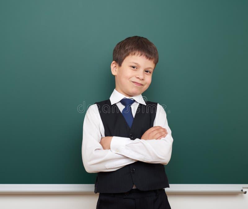 教育摆在干净的黑板,做鬼脸和情感的学生男孩,穿戴在一套黑衣服,教育概念,演播室phot 免版税图库摄影