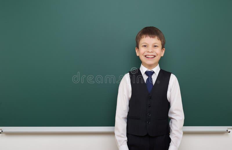 教育摆在干净的黑板,做鬼脸和情感的学生男孩,穿戴在一套黑衣服,教育概念,演播室phot 库存图片