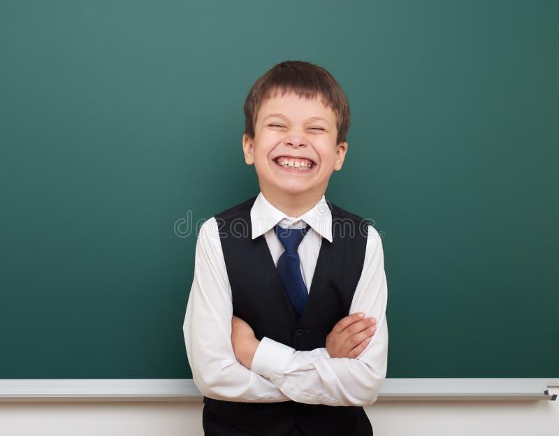 教育摆在干净的黑板,做鬼脸和情感的学生男孩,穿戴在一套黑衣服,教育概念,演播室phot 库存照片