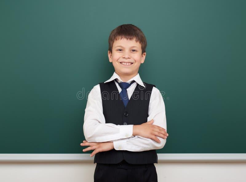 教育摆在干净的黑板,做鬼脸和情感的学生男孩,穿戴在一套黑衣服,教育概念,演播室phot 图库摄影