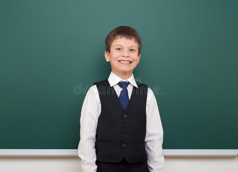 教育摆在干净的黑板,做鬼脸和情感的学生男孩,穿戴在一套黑衣服,教育概念,演播室phot 免版税库存照片