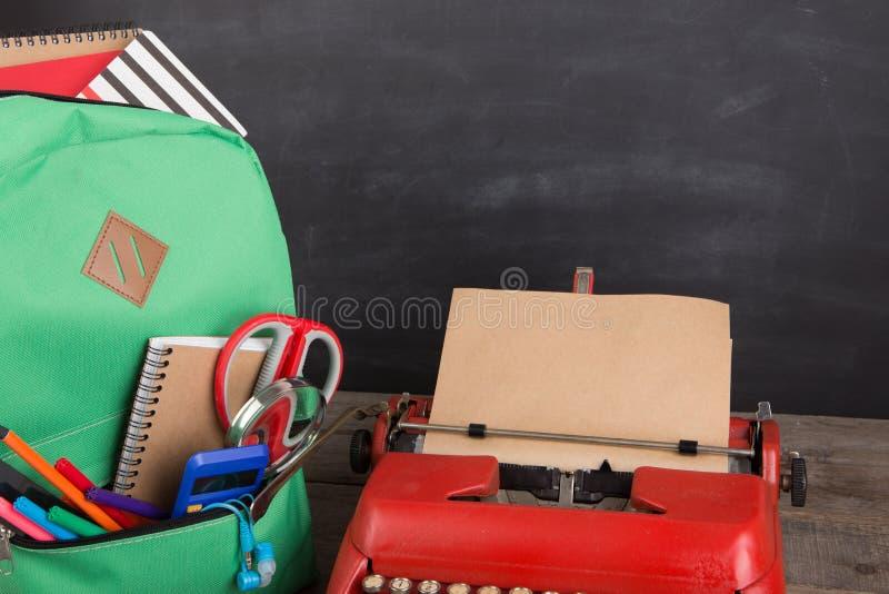教育概念-有书和其他供应的,黑板背景学校背包 免版税图库摄影