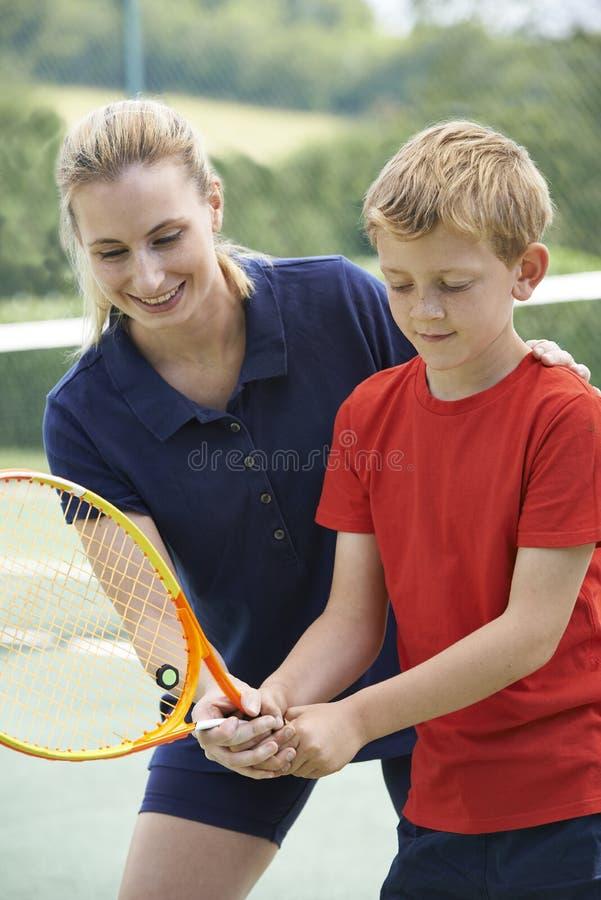 教育的女性网球教练男孩 免版税库存照片