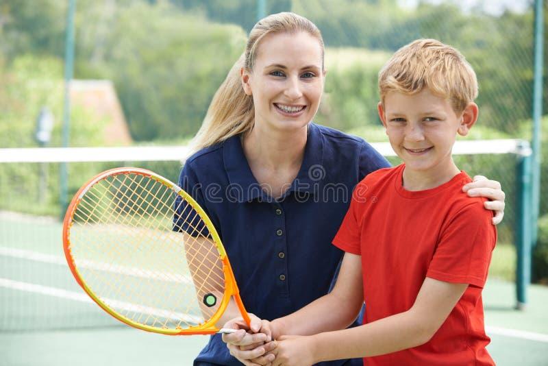 教育的女性网球教练男孩 图库摄影