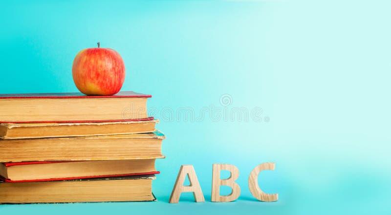 教育的概念 苹果、书和alphabe,蓝色背景,文本的地方,回到学校,拷贝空间 免版税库存图片