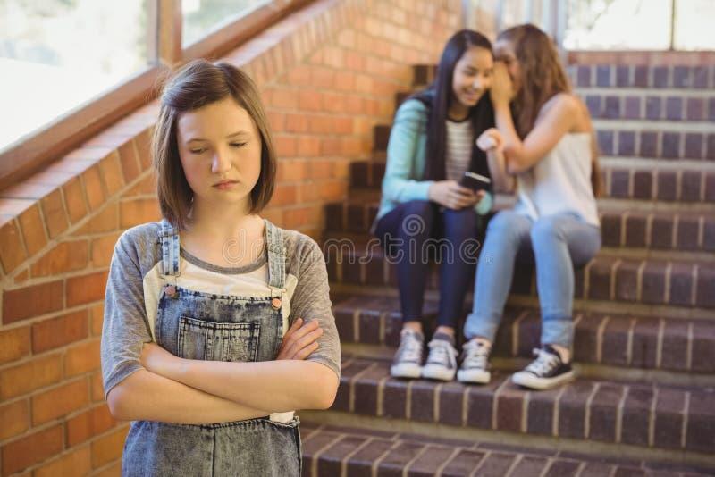 教育胁迫一个哀伤的女孩的朋友在学校走廊 免版税库存图片