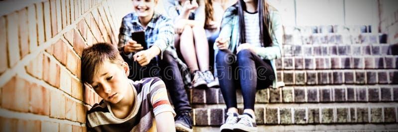教育胁迫一个哀伤的男孩的朋友在学校走廊 免版税库存图片